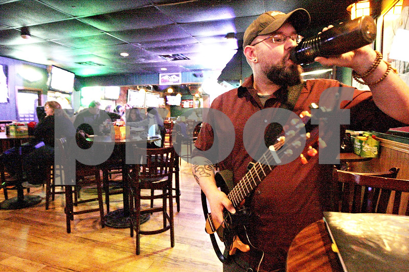Monica Maschak - mmaschak@shawmedia.com<br /> Brandon Weber, 32, of Rochelle, preps for his set during Open Mic Night at Fatty's in DeKalb on Monday, March 24, 2014.  Weber had previously played at Otto's and The House Cafe.