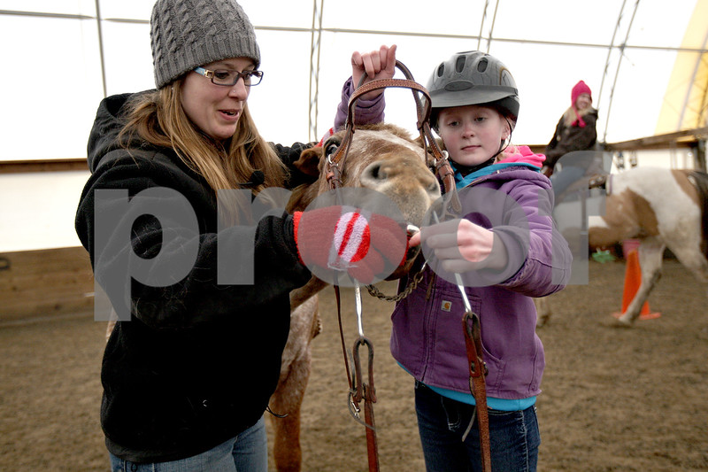 Monica Maschak - mmaschak@shawmedia.com<br /> Instructor Krissy Lowe helps Heidi Wood, 10, prep her horse, Ringo, to ride during an Advanced Spring Break Horse Camp at Runaway Ranch in Sycamore on Tuesday, March 25, 2014.
