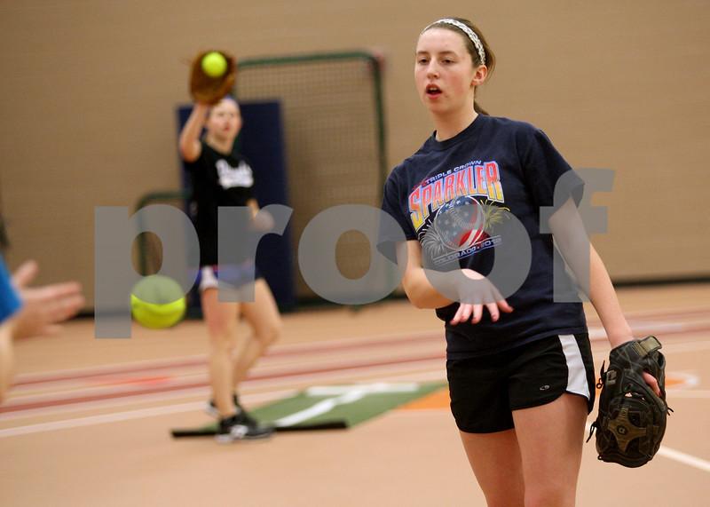 Monica Maschak - mmaschak@shawmedia.com<br /> DeKalb's senior Katie Kowalski warms up her arm during softball practice on Wednesday, March 19, 2014.