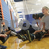 Danielle Guerra - dguerra@shawmedia.com   Genoa-Kingston junior midfielder Ashley Grimm talks to teammates while she puts her knee brace on before practice Tuesday morning in the gym. Grimm missed playing all of last season with a torn ACL.