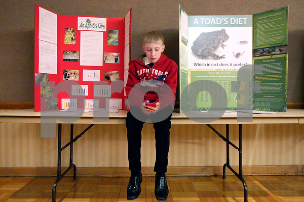 """Monica Maschak - mmaschak@shawmedia.com<br /> Gary Richardson, 13, an eighth grader from West Field Community School, sits next to his poster on """"An Aphid's Life"""" (left) as he waits for the lunch break to end during the 2014 Illinois Junior Academy of Science – Northern Region V Science Fair Regional Project Session Semi-Finals at the Holmes Student Center at Northern Illinois University on Saturday, March 22, 2014."""
