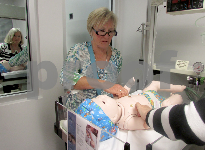 Andrea Azzo - aazzo@shawmedia.com<br /> Carol Quenett, of Genoa, looks at the baby simulator. In the reflection of the mirror, is Bette Chilton, Kishwaukee College dean of health and education.