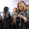 Monica Maschak - mmaschak@shawmedia.com<br /> Brittney Schmidt attaches the tassle to her cap before the Kishwaukee College graduation ceremony on Saturday, May 17, 2014. Schmidt received her certificate in architectural drafting.