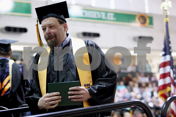 Monica Maschak - mmaschak@shawmedia.com<br /> Paul Belcher walks off the stage with his diploma at the Kishwaukee College graduation ceremony on Saturday, May 17, 2014. Belcher graduated with an Associate in Applied Science degree for automated engineering technology/computer numerical control.