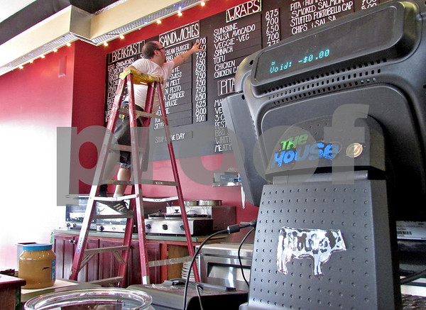 Katie Dahlstrom - kdahlstrom@shawmedia.com<br /> House Cafe co-owner Brian Fausett updates the cafe's menu on Tuesday to prepare for the grand reopening that will happen at 6 a.m. Friday.