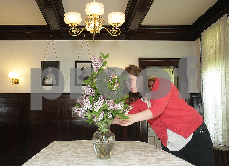 Danielle Guerra - dguerra@shawmedia.com <br /> Collections intern Allison Sutton places a vase of flowers in the dining room of the Ellwood-Nehring House which was opened to the public on Thursday, May 29, 2014, after a full year of restoration and construction work headed up by the Ellwood House Association in conjunction with the DeKalb Park District. Pictures of the house's first inhabitants, May and Perry Ellwood hang in the background.