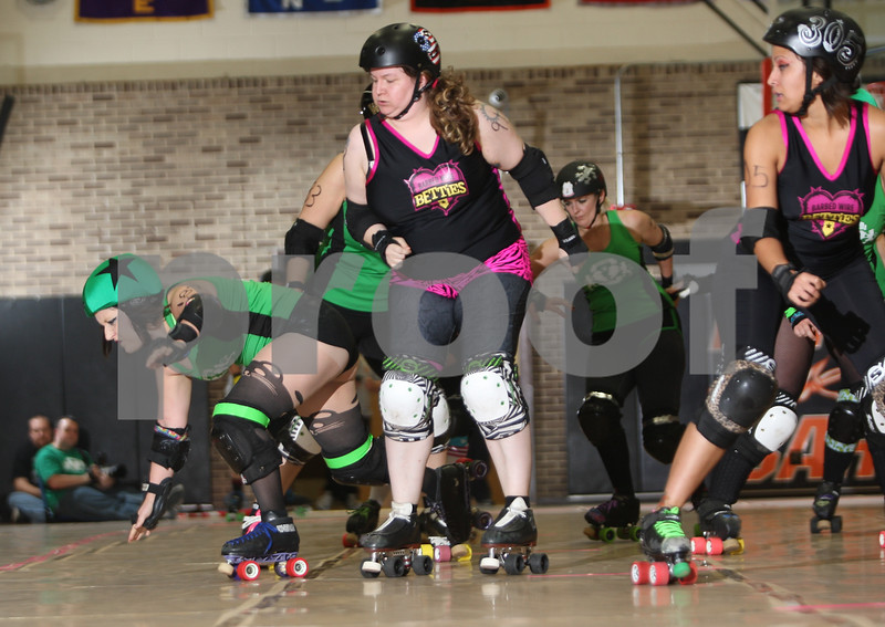 "Danielle Guerra - dguerra@shawmedia.com<br /> Barbed Wire Betties' Virginia Tilton, ""Demon,"" shoves down a DuPage Derby Dames' jammer during the Barbed Wire Betties' first home bout at Huntley Middle School in DeKalb on Saturday, November 8, 2014.  The Betties beat the Dames, 161-133."