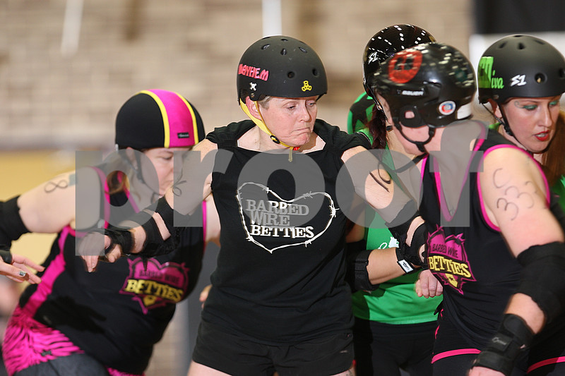 """Danielle Guerra - dguerra@shawmedia.com<br /> Lee Clark, """"Menopausal Mayhem,"""" helps block out the DuPage Derby Dames during the Barbed Wire Betties' first home bout at Huntley Middle School in DeKalb on Saturday, November 8, 2014.  The Betties beat the Dames, 161-133."""
