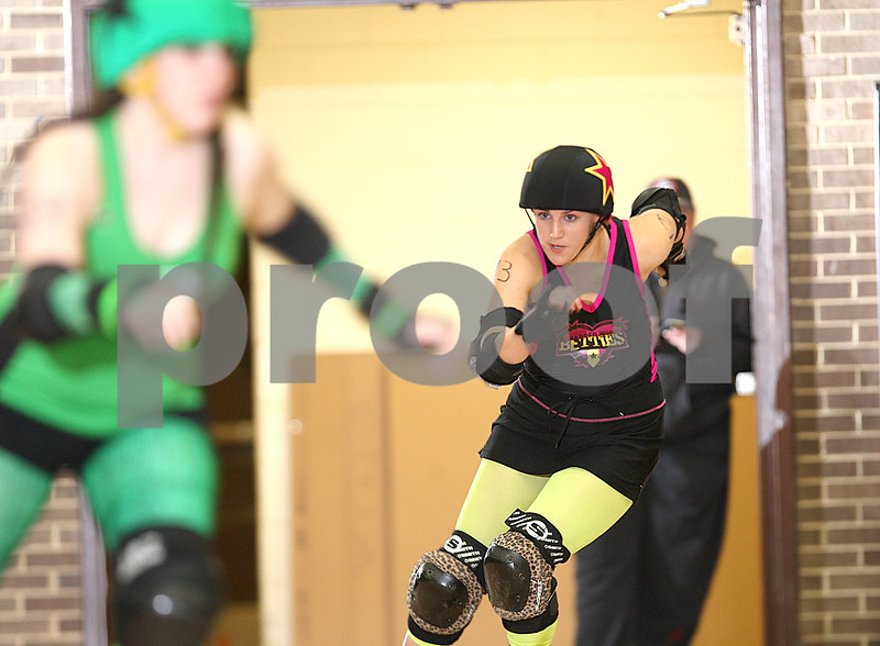 "Danielle Guerra - dguerra@shawmedia.com<br /> Barbed Wire Betties' Sarah Snow, ""Snowbeast,"" of Rochelle, tries the catch up to the DuPage Derby Dames' jammer during the first home bout at Huntley Middle School in DeKalb on Saturday, November 8, 2014.  The Betties beat the Dames, 161-133."
