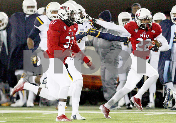 Monica Synett - msynett@shawmedia.com<br /> Northern Illinois wide receiver Aregeros Turner keeps a Toledo tackle at arms length on a 39-yard reception in the second quarter on Tuesday, November 11, 2014. The Huskies beat the Rockets, 27-24.