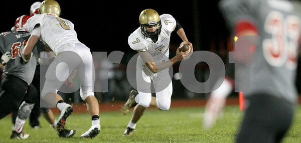 Monica Synett - mmaschak@shawmedia.com<br /> Sycamore quarterback Brett Bemis carries the ball in the second quarter against Yorkville on Friday, October 10, 2014.