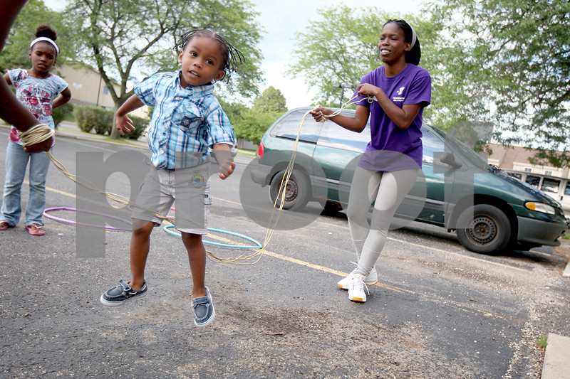 """Monica Synett - mmaschak@shawmedia.com<br /> Keyana Williams, 26, turns the jump rope for her 3-year-old son, Jeramie Green, outside of their apartment at University Village. Other children in the neighborhood like to gather and jump rope or hula hoop when Williams is outside playing with her children. """"It was something for me to start over again,"""" Williams said about University Village."""