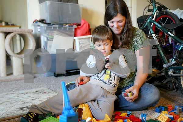 """Monica Synett - mmaschak@shawmedia.com<br /> Eve Besser, 35, plays with her 5-year-old son, Ziggy, in the living room of their two-bedroom apartment at University Village. Besser and her three children have bounced from place to place looking for a place to call their home, when she got the call saying she was approved for an apartment at University Village one year ago. """"It was like, this is mine,"""" Besser said."""