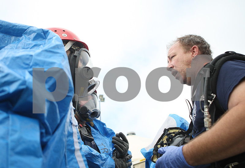 DeKalb firefighter Tom Conley (right) relays his team's findings to a second team to check the scene during the hazardous material drill at DeKalb Taylor Regional Airport on Thursday, Sept. 18, 2014. Danielle Guerra- dguerra@shawmedia.com