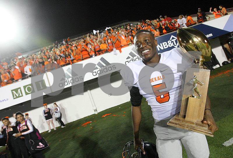 Danielle Guerra - dguerra@shawmedia.com<br /> DeKalb sophomore halfback Zuerek Day carries the Castle Challenge trophy back to the team after celebrating in front of the student section after DeKalb's 55-40 win over Sycamore at Huskie Stadium on Friday, September 19, 2014.