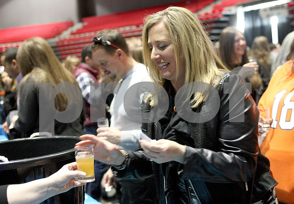 Monica Synett - msynett@shawmedia.com<br /> Lynnette Jackley, of DeKalb, tries a sample of McKenzie's Hard Cider during the annual America on Tap Beer Festival at the Convocation Center in DeKalb on Saturday, March 28, 2015. This is the festival's first year in DeKalb and the event sold out to 1600 people. Seventy four national and local breweries were represented at the event.