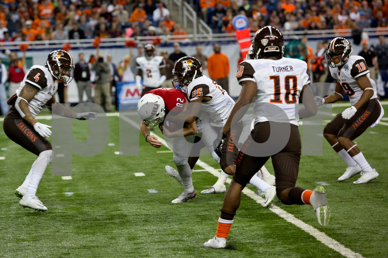 Laura McDermott for Shaw Media<br /> Northern Illinois University junior wide receiver Chad Beebe holds on to the ball while being taken down by Bowling Green University junior defensive back Alfonso Mack during the 2015 MAC Championship Game at Ford Field in Detroit, Mich. on Dec. 4, 2015. Bowling Green University beat Northern Illinois University 34-14.
