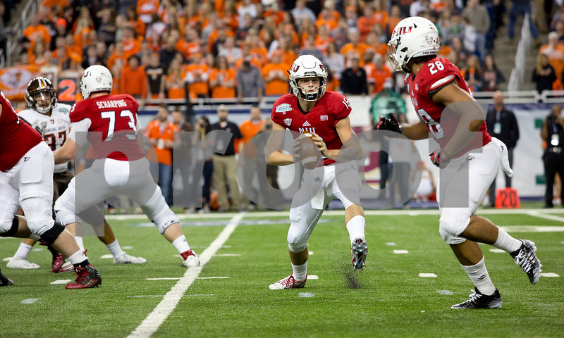 Laura McDermott for Shaw Media <br /> Northern Illinois University freshman quarterback Tommy Fiedler prepares  to pass the ball off to junior tailback Joel Bouagnon during during the first quarter at the 2015 MAC Championship Game against Bowling Green State University at Ford Field in Detroit, Mich. on Dec. 4, 2015.