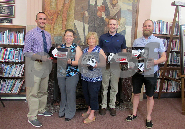 Brittany Keeperman - bkeeperman@shawmedia.com<br /> Members of Axletree, a nonprofit orginization, donates bicycle helmets to the DeKalb Public Library for the community's use on Thursday, May 7, 2015. From left: Dean Frieders, with Axletree, Edith Craig, Communications Manager at DeKalb library, Pat Adams, Department administrator at DeKalb Library, Aaron Nevdal, Axletree, Tobie DePauw North Centrall Cyclery and Axletree.