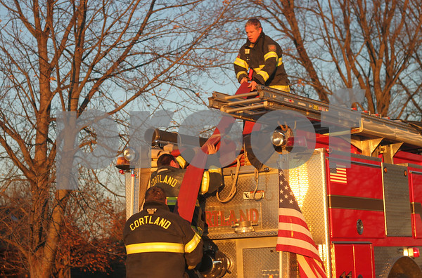 Katie Smith - ksmith@shawmedia.com<br /> Cortland firefighters let out fire hose to join efforts to extinguish a fire at a home 5400 block of east North Avenue in Cortland. Wind-aided flames reached nearly 20 feet before firefighters controlled the blaze.
