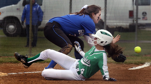 Geneva third baseman Molly Wrenn fields a throw from the outfield as York's Katherine Karnatz slides safely into the bag for a triple during a game in Geneva on March 28.
