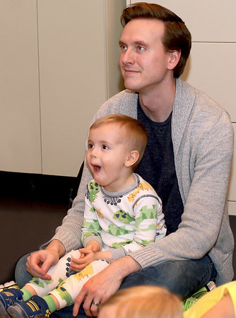 Henry Van Dyke, 2, and his dad Phillip enjoy listening to a story at Pajama Story Time at the St. Charles Public Library on April 7.