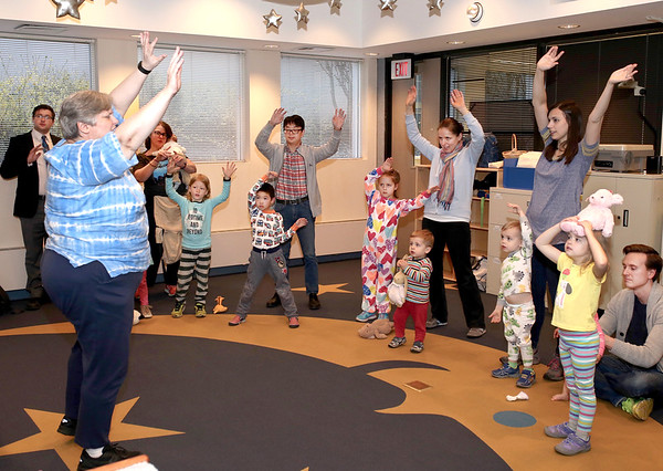 Youth Services Librarian Carol Leeson gets families on their feet during Pajama Story Time at the St. Charles Public Library on April 7.