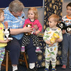 Youth Serives Librarian Carol Leeson passes out stuffed animals to Makayla Connolly, 4, Hailey Connolly, 1, Henry Van Dyke, 2 and Kevin Lu, 5 so they can be active participants in a story she is about to read on April 7. Participants were invited to come dressed in their pajamas to Pajama Story Time at the St. Charles Public Library.