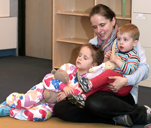 Maria and Milosz Piechota snuggle their favorite stuffed toys and cuddle up with their mom Karolina, as they listen to stories during Pajama Story Time at the St. Charles Public Library on April 7.