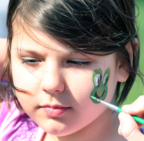 Isabella Paris, 7, of Wheaton has a frog painted on her face during an Egg Hop at the Peg Bond Center in Batavia April 15.