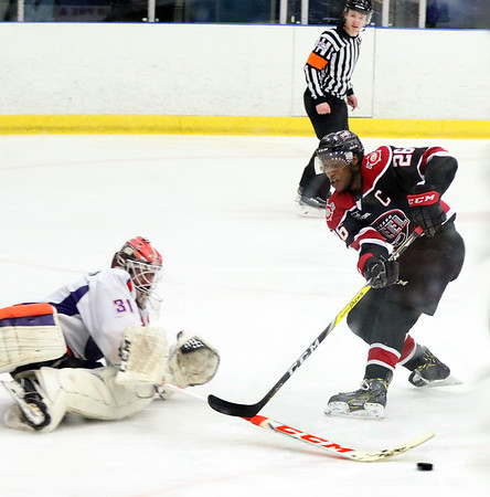 Chicago Steel's Marc Johnstone has the puck knocked away by Youngstone goalie Ivan Kulbakov during game one of the USHL's Western Conference semifinal against Youngstown at the Fox Valley Ice Arena. The Steel won 4-1.