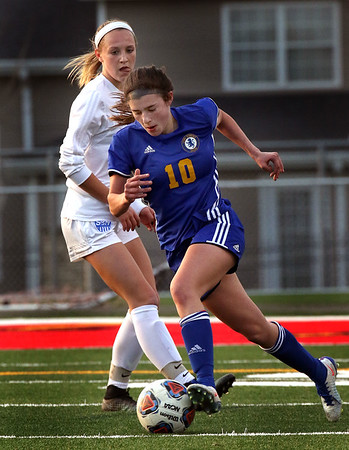 Lyons' Bella Lestina moves past St. Charles North's Hailey Rydberg during a game at Batavia High School on April 13.