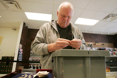 "Mike Greene - mgreene@shawmedia.com Madison, WI resident Cal Flach (cq) inspects coins before making a purchase at Marengo Coin Shop Thursday, April 5, 2012 in Marengo. Flach travels the distance to the shop because he believes the owner, Dominic Debock (cq), is ""honest, fair and treats you well."""
