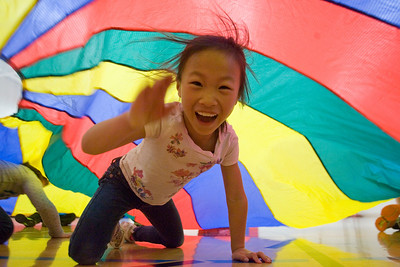 Mike Greene - mgreene@shawmedia.com Emma Fang, 7, crawls under a parachute while playing a game as part of a kick-off event held Friday, April 6, 2012 to promote health and nutrition at Woodscreek School in Crystal Lake. The event was made possible by a grant given to the McHenry County Department of Health by the American Cancer Society.