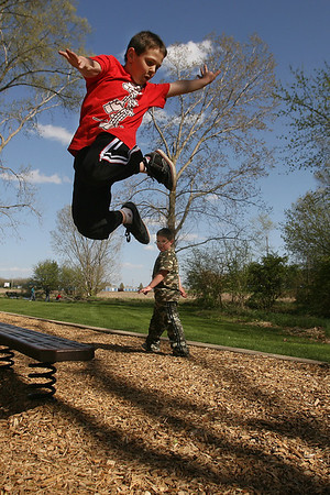 Mike Greene - mgreene@shawmedia.com Jakson Bennett (cq), 7, does a stunt off a bench as his brother Alex Bennett, 6, watches on at Barbara Key Park Monday, April 9, 2012 in Lake in the Hills.