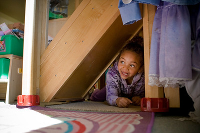 Mike Greene - mgreene@shawmedia.com Chloe Soto-Garcia, 4, peeks out from underneath a staircase while playing at House of Children Tuesday, April 10, 2012 in Woodstock. Enrollment costs for more than half of the children at House of Children are subsidized by state funds.