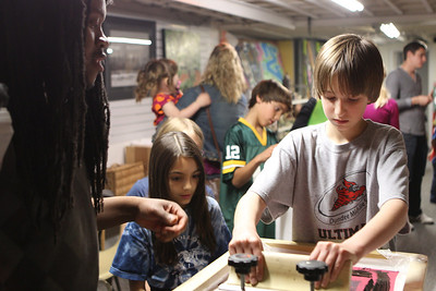 Mike Greene - mgreene@shawmedia.com Dundee Middle School student John Florence, 13, works on a screen shirt during a D300 gallery exhibit at River Art Studio & Gallery Friday, April 13, 2012 in Algonquin. Florence was being guided through the process by instructor Freddrick Wimms, of Woodstock.
