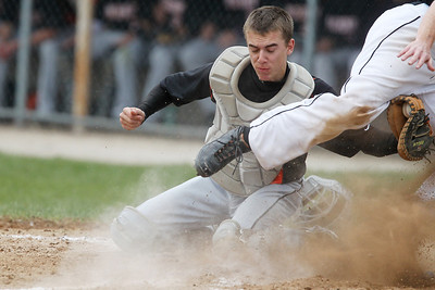 Mike Greene - mgreene@shawmedia.com McHenry's Cody Freund braces during a collision at the plate with Crystal Lake Central's Josh Reilly Friday, April 13, 2012 in Crystal Lake. McHenry won the game 5-3.