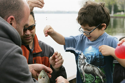 Mike Greene - mgreene@shawmedia.com Ari Shamash, 6, gets help from his dad Sande (center) and Tony Mrkvicka unhooking a fish he caught during the annual Veteran Acres Family Fishing Derby Saturday, April 14, 2012 in Crystal Lake.