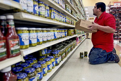 Sarah Nader - snader@shawmedia.com Employee Rene Aguino of Johnsburg stocks the shelves with jars of pickles while working at Angelo's Fresh Market in Johnsburg on Wednesday, April 18, 2012. Angelo's opened in December and will be having a grand opening early next month.