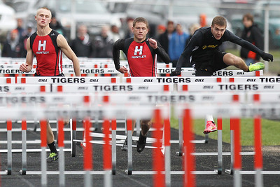 Mike Greene - mgreene@shawmedia.com Huntley's Jake Brock (left) and Chase Hellinger race with Harvard's Nathan Baldwin in the boys 110 meter high hurdles final during the McHenry County Track & Field Meet Friday, April 20, 2012 in Crystal Lake. Huntley's Chase Hellinger took first place in the event.