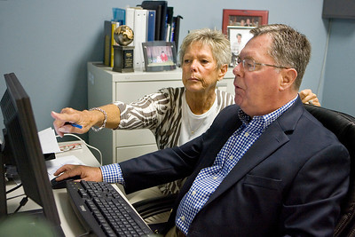 Mike Greene - mgreene@shawmedia.com Pam Doherty points out an issue to Dick Doherty, her husband, while troubleshooting an in-office computer system Wednesday, April 25, 2012 at Crystal Lake Travel in Crystal Lake. The couple has worked together at the office for 17 years.