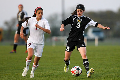 Daniel J. Murphy - dmurphy@shawmedia.com   Huntley midfielder Delaney Loprieno (left) and Jacobs' Kelly Grady chase down the ball in the first half Thursday April 26, 2012 at Huntley High School. Huntley defeated Jacobs in a shootout.
