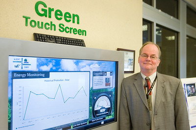 Mike Greene - mgreene@shawmedia.com John Hadley, Director of Facilities Management for McHenry County, stands next to one of the green initiative his department has implemented Thursday, April 26, 2012 in Woodstock. The green touch screen allows users to monitor the building's energy efficiency and how much energy is being generated by solar panels on the buildings roof.