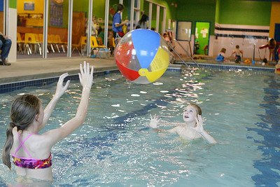 Mike Greene - mgreene@shawmedia.com Jenna Walker (right), 11, and her sister Jamie, of Cary, play with a beach ball during a Customer Appreciation party at Dolphin Swim Club Sunday, April 29, 2012 in Crystal Lake. Dolphin Swim Club offers swim lessons and open swim sessions as well as hosting birthday parties.