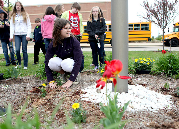 Geneva Middle School North seventh-grader Paulina Kulyavtsev plants flowers with her class outside the school Friday in honor of Earth Day.