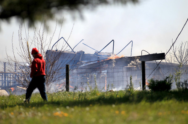 A man walks past one of two barns that caught fire in Elburn Monday morning.