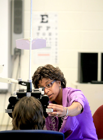 Sandy Bressner - sbressner@shawmedia.com<br /> Dr. Carla Adams of St. Charles gives an eye examination to a student at Richmond Elementary School in St. Charles Thursday morning. The free clinic was part of a visit by Transitions Optical and VSP Vision Care.