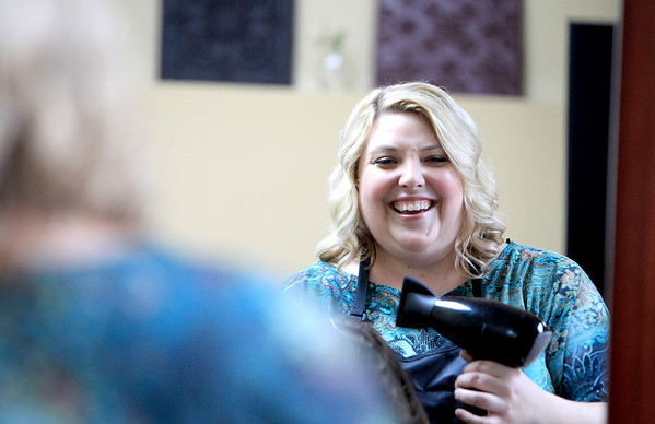 Renee Martinez, who co-owns the Shear Ambition salon in Batavia with her husband Freddy, laughs with client Mary Stevenson of Sugar Grove while blow drying her hair at the salon Wednesday.
