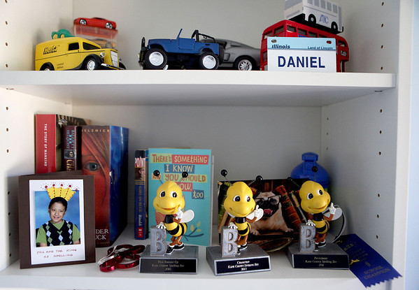 Trophies from past Kane County Spelling Bee events line the bookshelf of 2012 winner Daniel Oster Batavia bedroom. Oster, who has cerebral palsy, will compete in the Scripps National Spelling Bee next month in Washington, D.C.